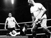 Huang (foreground) defending a challenge by a wrestler (on the ground). Yek Sing Ong (background) was the referee representing Huang.